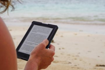 woman looking at content on ipad at the beach