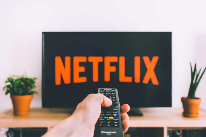 television with Netflix logo and hand of man holding tv remote