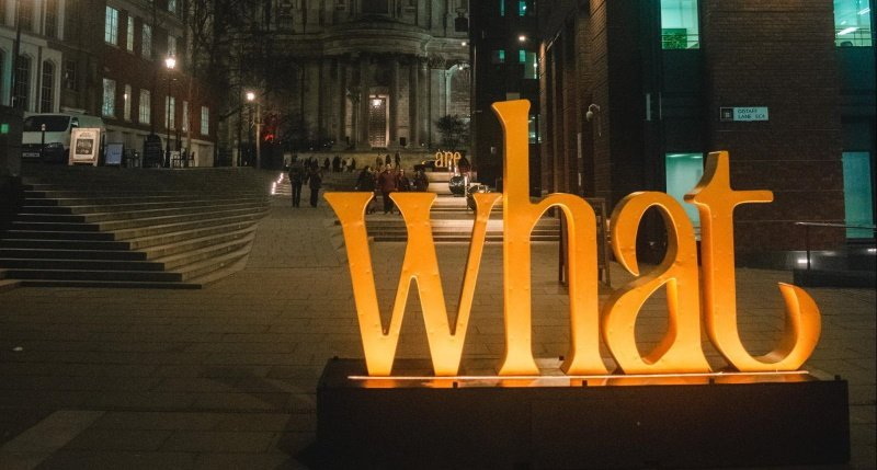 """illuminated sign that says """"what"""" to represent what to post on LinkedIn stories"""